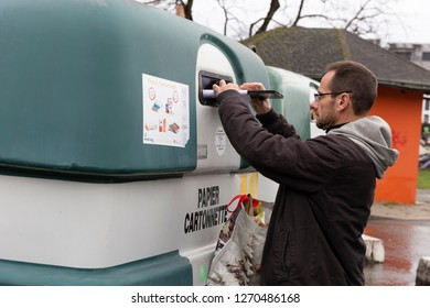 Gex, France - 22 December, 2018: A european resident throws out paper waste into a separated contaner for recycling