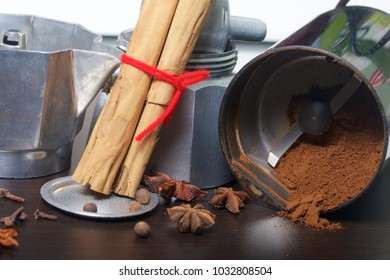 A geyser coffee machine in disassembled form is on the table. It is visible ground coffee in a coffee grinder and spices: a anise, a carnation,  cinnamon and fragrant pepper.