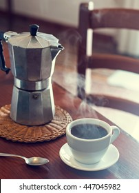 Geyser coffee maker and cup of black coffee on the wooden table, retro toned photo