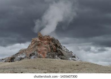 Geyser erupting with steam and dark, cloudy sky.