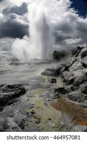 A geyser erupts merging with the clouds above at a hotspot in Rotorua, North Island New Zealand