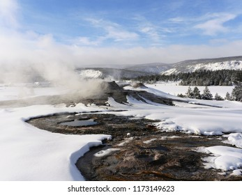 Geyser and hot spring in a snowy landscape - Yellowstone National Park, USA, in winter