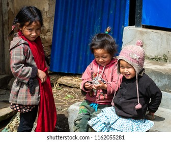 GHALEGAUN, NEPAL - CIRCA MAY 2018: Three young Nepali girls playing outside their home.