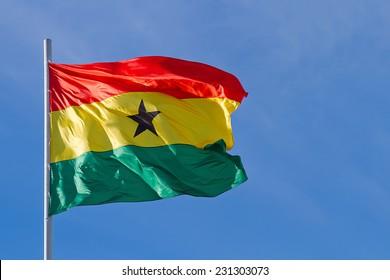 Ghana flag is waving in front of blue sky