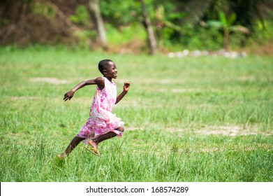 GHANA - MARCH 3, 2012: Unidentified Ghanaian girl runs happily in the field in Ghana, on March 3rd, 2012. Children in Ghana suffer from poverty due to the unstable economical situation