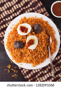Ghana rice jollof dish with shito sauce, beef and boiled egg