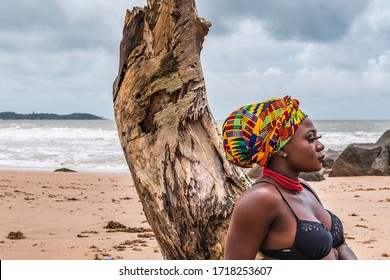 Ghanaian African woman with colorful headdress sitting at a broken palm tree stump at the beach in Axim Ghana West Africa