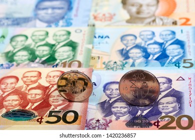 Ghanaian coins on the background of banknotes