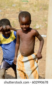 GHANI, GHANA - JAN 14, 2017: Unidentified Ghanaian two little boys in old clothes in a local village. Ghana people suffer of poverty due to the bad economy.