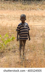 GHANI, GHANA - JAN 14, 2017: Unidentified Ghanaian a little boy stands near a dry grass in a local village. Ghana people suffer of poverty due to the bad economy.