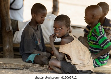 GHANI, GHANA - JAN 14, 2017: Unidentified Ghanaian little boy in dirty clothes looks around in the Ghani village. Ghana children suffer from poverty due to the bad economy.