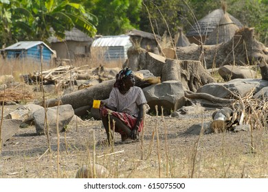 GHANI, GHANA - JAN 14, 2017: Unidentified Ghanaian woman holds a yellow cup in her hands in the Ghani village. Ghana people suffer of poverty due to the bad economy.