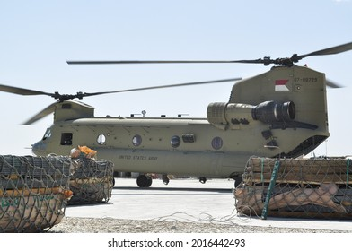 GHAZNI, AFGHANISTAN - April 5, 2011: A US Army Boeing CH-47 Chinook sits on a airfield surrounded by supplies that prepared to be sling loaded  to another location during the war in Afghanistan.