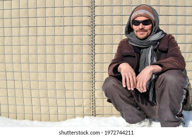 GHAZNI, AFGHANISTAN - February 15, 2011: An Afghan man rests against a US military hesco barrier at Forward Operating Base Ghazni during the war in Afghanistan.