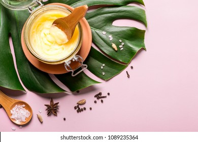 ghee butter in a glass jar, pink salt and spices on pink background.