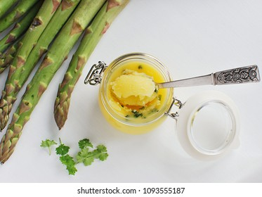 Ghee butter with parsley in glass jar ready for cooking. Homemade clarified butter and asparagus.