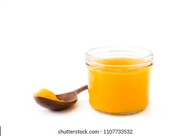 Ghee or clarified butter in jar and wooden spoon isolated on white background
