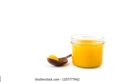 Ghee or clarified butter in jar and wooden spoon isolated on white background. Copyspace