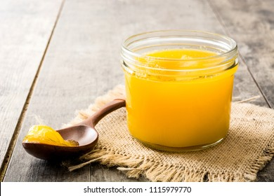 Ghee or clarified butter in jar and wooden spoon on wooden table.