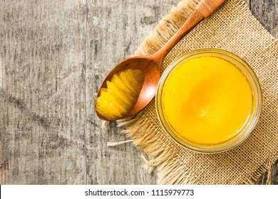 Ghee or clarified butter in jar and wooden spoon on wooden table. Top view. Copyspace