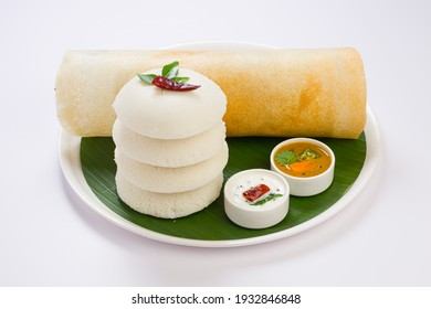 Ghee roast  Dosa and Idlii, south indian main breakfast item which is beautifully arranged in a white plate lined with banana leaf  and curry as sambar and chutney on white background.