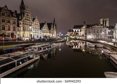 GHENT, BELGIUM - 18TH FEB 2016: A view towards Sint-Michielskerk (Saint Michael's Church, Ghent) in Ghent at night from the Graslei and Korenlei. Boats and other buildings can be seen.