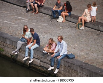 Ghent, Belgium - 26 August 2017: People sitting by the canal in Ghent