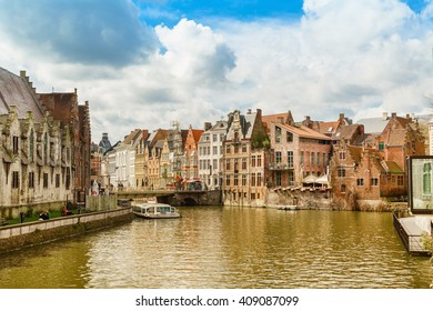 Ghent, Belgium - April 12, 2016: Old houses along canal and boat with tourists in popular touristic destination Ghent, Belgium