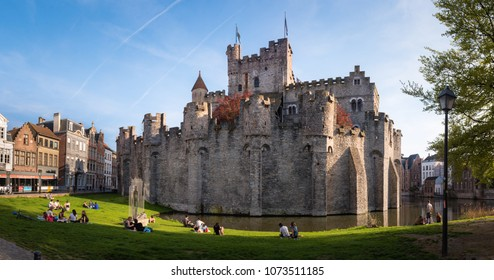 GHENT, BELGIUM. April 18, 2018. Medieval castle of the counts (Gravensteen castle) in historical city center Ghent. Young people sitting, talking drinking in park Gravensteen. Ghent, Flanders, Belgium