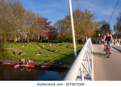 GHENT, BELGIUM. April 18, 2018. Bike bridge over river Schelde to small park Keizerpark in Ghent. Young people gather in Keizerpark for drinks, picnic barbecue or just for sunbathing. Biking on bridge