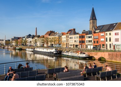 GHENT, BELGIUM. April 18, 2018. Portus Ganda harbor in Ghent. People enjoy a sunny summer day together with friends sittings on benches along the canal and yacht harbour Portus Ganda in Ghent, Belgium