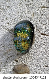 Ghent, Belgium - August 12, 2018: Human face orgonite made from transparent material and shiny objects glued to a wall.