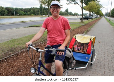 Ghent, Belgium - August 17, 2018: a Belgian father on a bicycle carries his two little smiling daughters in a bicycle carriage. Family bike ride.