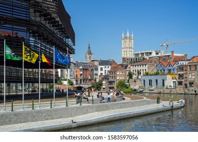 Ghent, Belgium. August 2019. Young people in front of the public library De Krook, and view over the belfry and St Bavo Cathedral towers in the city Ghent, East Flanders, Belgium