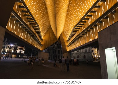 Ghent, Belgium - August 28, 2017: Abstract illuminated wood ceiling of the municipal pavilion or Stadshal at night with people around in the old town of the medieval city of Ghent, Belgium