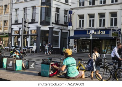 Ghent, Belgium - August 28, 2017: Worker of Deliveroo resting with people walking and cycling in the old town of the medieval city of Ghent, Belgium