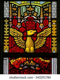 GHENT, BELGIUM - DECEMBER 23, 2016: Stained Glass window depicting a Phoenix rising from the Ashes, in the Cathedral of Saint Bavo in Ghent, Flanders, Belgium.