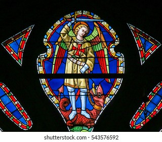 GHENT, BELGIUM - DECEMBER 23, 2016: Stained Glass depicting Saint Michael the Archangel slaying Satan, presented as a dragon, in the Cathedral of Saint Bavo in Ghent, Flanders, Belgium.