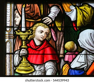 GHENT, BELGIUM - DECEMBER 23, 2016: Stained Glass window depicting an Altar Boy holding a Candelabrum in the Cathedral of Saint Bavo in Ghent, Flanders, Belgium.