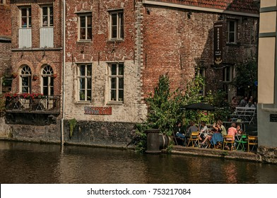 Ghent, Belgium - July 03, 2017. Old buildings in front of the canal and people in Ghent. In addition to intense cultural life, the city is full of Gothic and Flemish style buildings. Northern Belgium.