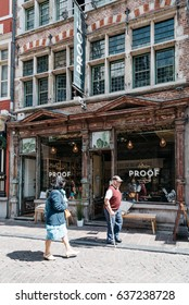 Ghent, Belgium - July 31, 2016: Old shop with people walking by in a street in historical city centre of Ghent