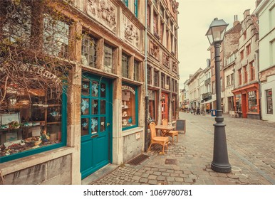GHENT, BELGIUM - MAR 30, 2018: Old street lantern and brick house with reliefs on wall and small store with colorful doors on March 30, 2018. Ghent is the capital city of the East Flanders province
