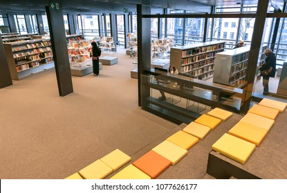 GHENT, BELGIUM - MAR 30, 2018: Muslim woman reading inside the new public library De Krook with bookshelves and lounge on March 30, 2018. Ghent is capital city of the East Flanders province