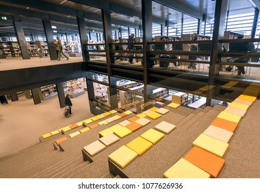 GHENT, BELGIUM - MAR 30, 2018: Readers watching the books inside the new public library De Krook with bookshelves and lounge on March 30, 2018. Ghent is capital city of the East Flanders province