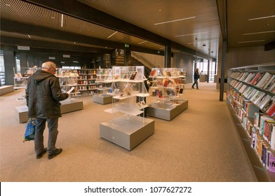 GHENT, BELGIUM - MAR 30, 2018: Elderly man reading the books inside the new public library De Krook with bookshelves and lounge on March 30, 2018. Ghent is capital city of the East Flanders province