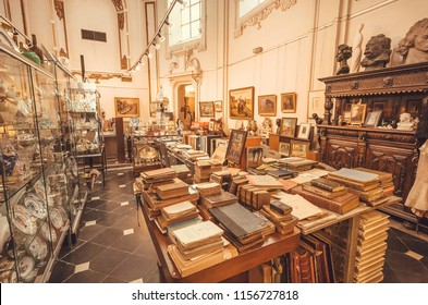 GHENT, BELGIUM - MAR 30, 2018: Interior of an antique shop in historical church with rare books, porcelain, paintings and retro furniture on March 30 2018. Ghent is capital city of East Flanders province