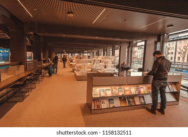 GHENT, BELGIUM - MAR 30, 2018: Reader watching bookshelf with new books inside the public library De Krook with bookshelves on March 30, 2018. Ghent is capital city of the East Flanders province