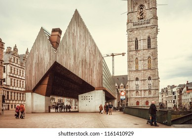 GHENT, BELGIUM - MAR 30, 2018: Modern architecture concert hall STADSHAL and people walking around old city on March 30, 2018. Ghent is the capital city of the East Flanders province