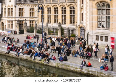 GHENT, BELGIUM. March 24, 2018. Young people gather together with friends for drinks at Graslei along the canal in historical city center of Ghent, Flanders, Belgium.
