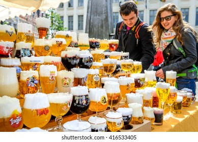 Ghent, Belgium - May 03, 2014: Couple of tourists picking up candles made in form of a traditional glass of Belgium beer.